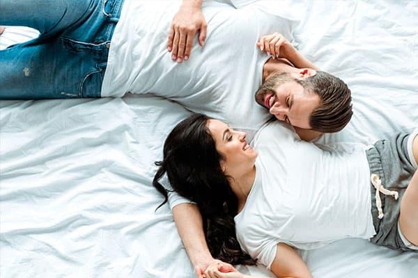 Mann und Frau liegen glücklich im Bett und überlegen, wie sie die Einnistung fördern können.