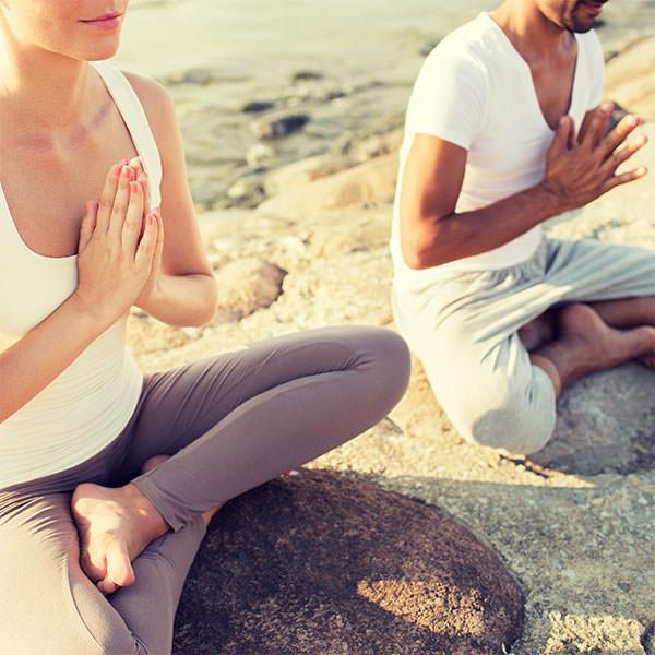Paar meditiert gemeinsam am Strand - mit Ruhe können Sie die Einnistung der befruchteten Eizelle fördern.