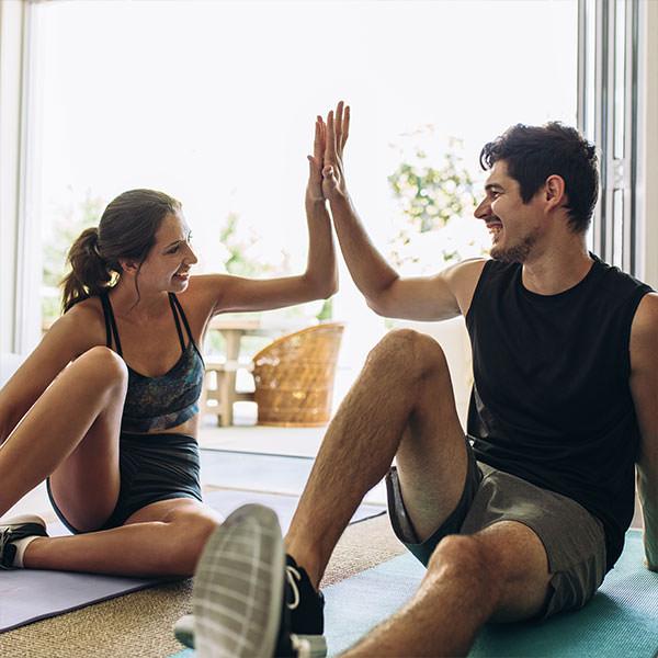 Paar möchte seine Fruchtbarkeit erhöhen und klatscht sich auf der Yogamatte ab.
