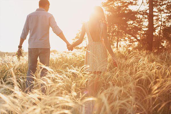 Paar läuft gemeinsam durch ein Feld - der unerfüllte Kinderwunsch belastet die Psyche.