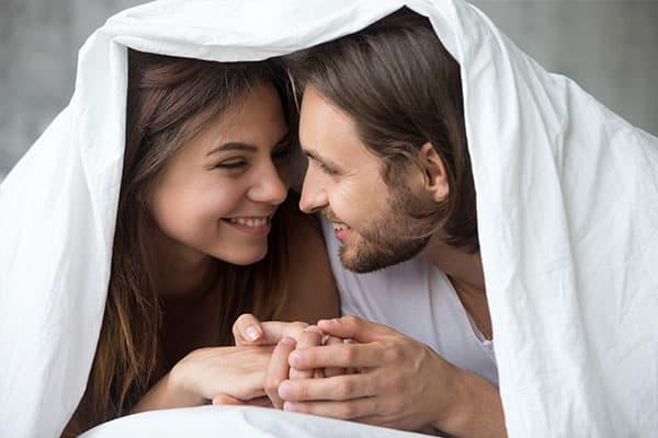 Ein Paar weiß, welche Fruchtbarkeits-Mythen wahr und welche falsch sind, und steckt gelassen die Köpfe unter der Bettdecke zusammen.