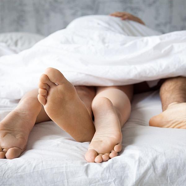 Mann und Frau genießen den Geschlechtsverkehr, weil sie über die falschen Kinderwunsch-Mythen Bescheid wissen.