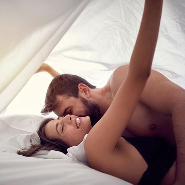 Paar unter der Bettdecke freut sich über Tipps, um natürlich schwanger zu werden.