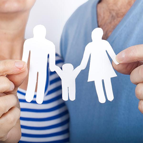 Paar mit spätem Kinderwunsch hält eine Papier-Familie in den Händen.