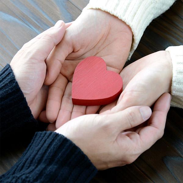 Die Hände einer Frau liegen in Männerhänden und darin ist ein kleines Herz - es steht für den unerfüllten Kinderwunsch.